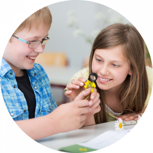 boy and girl in a classroom examining a yellow flower with a magnifying glass