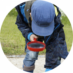 kid with blue hat outside bent over looking at the ground through magnifying glass